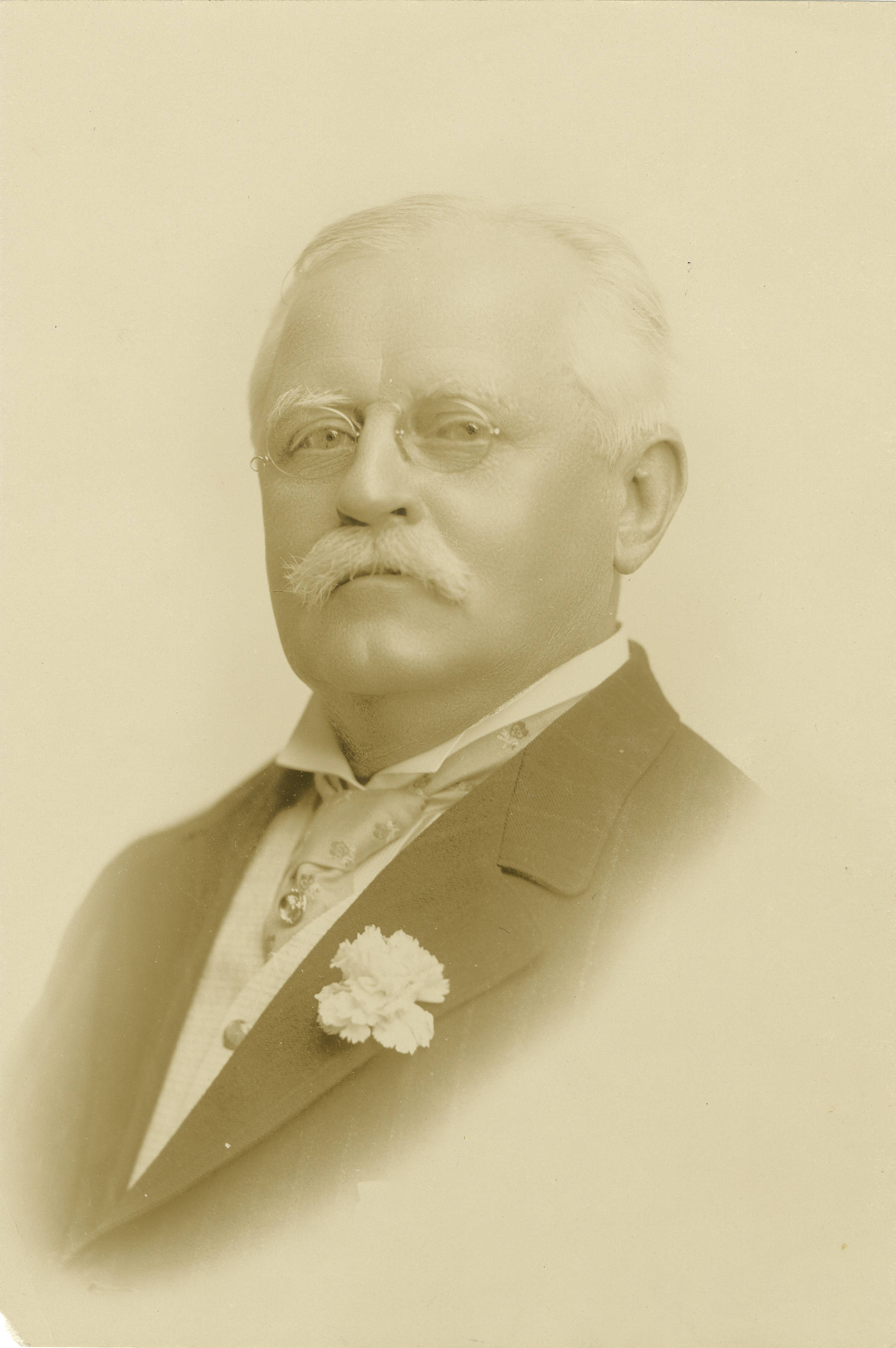 """A posed portrait of a man with short gray hair and mustache, wearing a jacket, necktie with pin, pince-nez eyeglasses, and a carnation on his jacket lapel, facing left and looking at the camera."" Source: The Carolina Story."