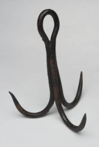 """This hook was once used on a """"grab rope' to retrieve the bucket in UNC's Old Well whenever the bucket became ditached from its pullet rope or chain.""""Treble hook, wrought iron. 1800s, from UNC's Old Well,"""" in North Carolina Collection, Wilson Library, UNC-Chapel Hill."""